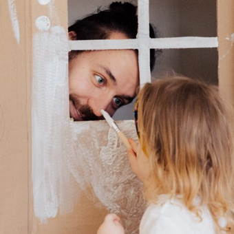 A child painting a man's nose through the window of a carboard house